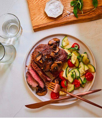 steak with sautéed zucchini and tomato